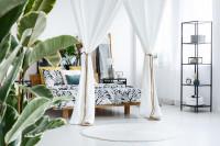 Drevená posteľ a kovový regál v spálni s bielymi závesmi