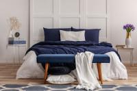 Čalúnená lavica v priestrannej modro-bielej spálni