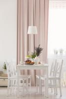 Biely jedálenský stôl a stoličky s ružovým závesom