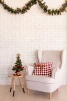 Biele kreslo ušiak a drevený odkladací stolík s vianočnou výzdobou