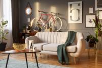 Svetlá pohovka v kontraste so sivou stenou a retro stolík
