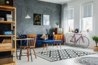Modrá pohovka v obývačke so štýlovou sivou stenou