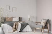 Retro kreslo s podrúčkami vo svetlej škandinávskej spálni