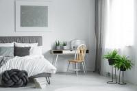 Sivá čalúnená posteľ v bielej škandinávskej spálni
