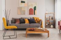 Sivá pohovka a žltá stolička v retro obývačke
