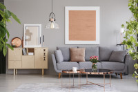 Sivá pohovka a okrúhle kovové stolíky v retro obývačke