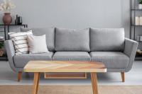 Drevený stolík a sivá pohovka s dekoračnými vankúšmi