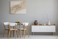 Drevený jedálenský stôl so stoličkami a nízka biela komoda