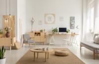 Sivé kreslo a drevený písací stôl v škandinávskej obývačke