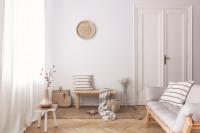 Svetlá pohovka v bielej obývačke s prírodnými doplnkami
