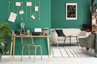 Pracovný stôl v obývačke s výraznou zelenou stenou