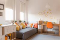 Písací stôl a stolička vo svetlej detskej izbe s oranžovými doplnkami
