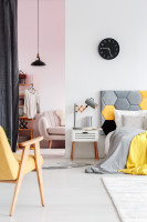 Čalúnená posteľ a biely nočný stolík v škandinávskej spálni