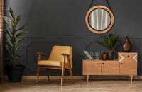 Žlté kreslo a okrúhle zrkadlo v sivej retro obývačke