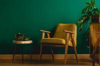 Žlté retro kreslo a okrúhly stolík v zelenej obývačke