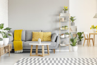 Okrúhly stolík a sivá pohovka so žltými doplnkami