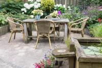 Drevený stôl a ratanové stoličky na vidieckej terase