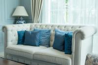 Čalúnená biela pohovka s modrými vankúšmi