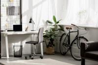 Biely písací stôl a stolička na kolieskach vo vzdušnej pracovni