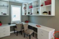 Biele pracovné stoly a čalúnené stoličky v pracovni so sivou stenou