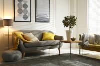 Pohovka so žltými vankúšmi v bielo-sivej obývačke