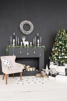 Čalúnené kreslo v obývačke s tmavosivou stenou a bielou vianočnou výzdobou