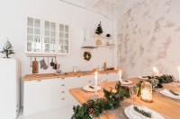 Biela kuchynská linka a drevený jedálenský stôl s vianočnými dekoráciami