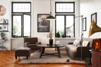 Hnedé kreslo, gauč a veľký okrúhly stolík v retro obývačke