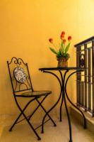Kovová stolička a okrúhly stolík na žltom balkóne s tulipánmi