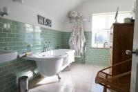 Vaňa na nožičkách v zeleno-bielej retro kúpeľni