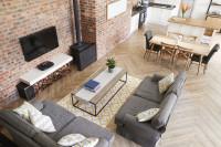 Sivé pohovky v rustikálnej obývačke s tehlovou stenou