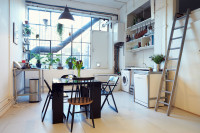Čierny stôl a stoličky v industriálnej kuchyni
