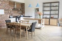 Drevený jedálenský stôl a stoličky v priestrannej kuchyni s tehlovou stenou