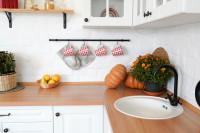 Biela kuchyňa s drevenou doskou a jesennými doplnkami