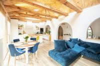 Okrúhly jedálenský stôl a modré stoličky v rustikálnom interiéri