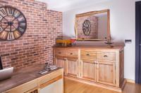 Masívna drevená komoda v obývačke s tehlovou stenou