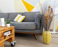Drevený stolík na kolieskach a pohovka so žltými doplnkami