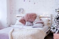 Drevená manželská posteľ s huňatými dekoračnými vankúšmi a pletenou dekou