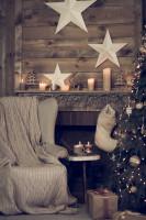 Svetlé kreslo ušiak s pletenou dekou a vianočnými dekoráciami