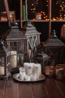 Biele sviečky a sada drevených lampášov v rustikálnom štýle