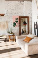 Nízka pohovka v obývačke s bielou tehlovou stenou