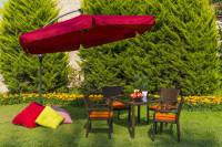 Ratanový stôl a stoličky s oranžovými podsedákmi