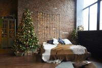 Posteľ a vianočný stromček v spálni s tehlovou stenou