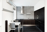 Tmavá kuchynská linka a biely stôl v modernej kuchyni