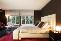 Masívna biela posteľ v spálni s čiernymi stenami