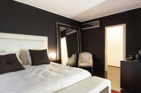 Biela manželská posteľ v modernej čiernej spálni