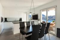 Čierny jedálenský stôl v kontraste s bielou kuchyňou