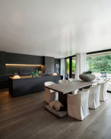 Dlhý jedálenský stôl a biele stoličky v čiernej kuchyni