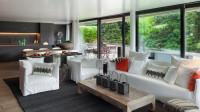 Biela pohovka a kreslá vo veľkej obývačke s kuchyňou
