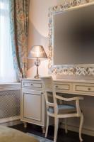 Veľké zrkadlo a svetlý nábytok v barokovej spálni